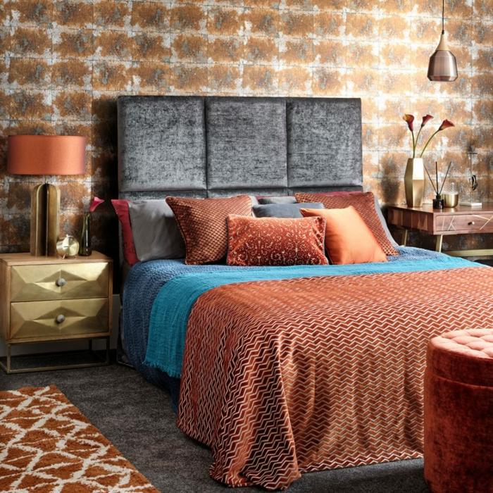cama con cabecero en gris oscuro, paredes con papel pintado, habitacion matrimonio en colores calientes