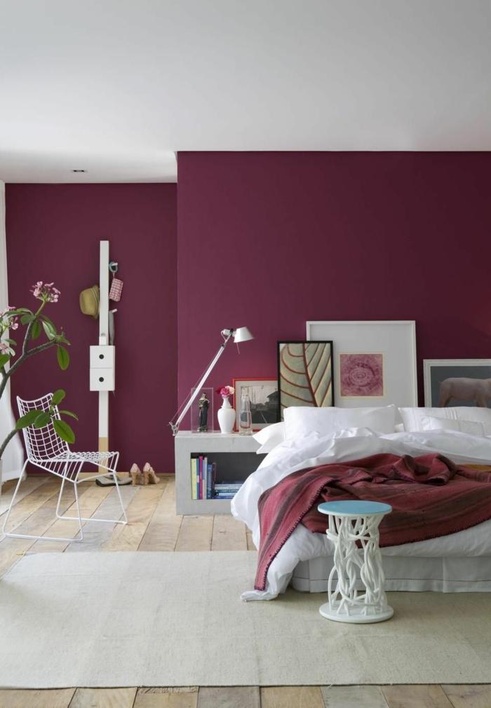 decoracion de dormitorios con paredes en color borgoña con alfombra en beige y suelo de parquet