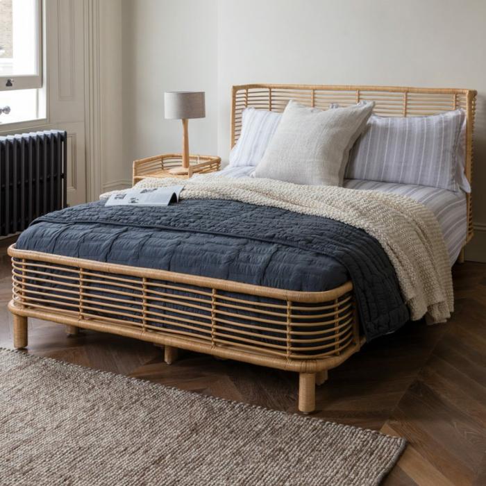 cama de madera moderna con cabecero, habitacion matrimonio con suelo de parquet y alfombra marrón