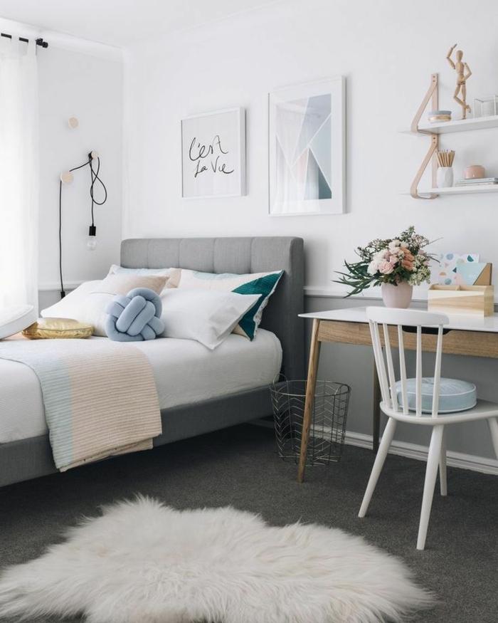 decoracion de habitacion con cama con cabecera alta en gris con alfombra de animal en blanco, escirotio con silla