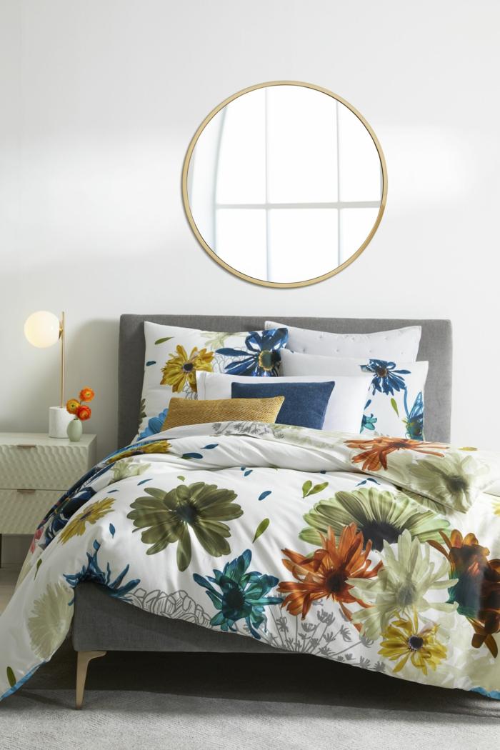 ideas sobre como decorar una habitacion pequeña, grande espejo moderno en forma oval, sábanas estampados flores