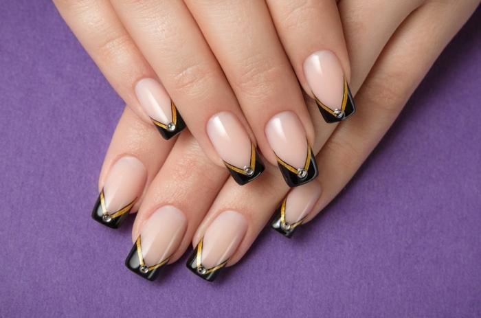 uñas acrilicas decoradas en negro y dorado, uñas muy largas con esmalte transparente y puntas en negro