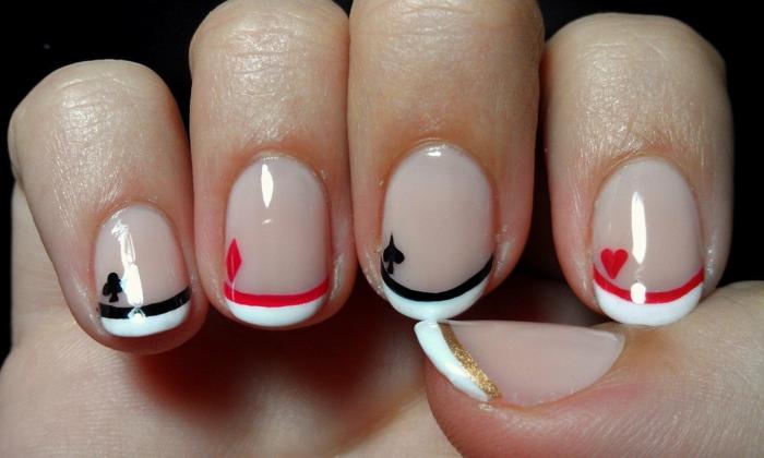 uñas acrilicas decoradas con elementos originales, uñas cortas ovaladas con puntas en blanco y elementos en negro y rojo