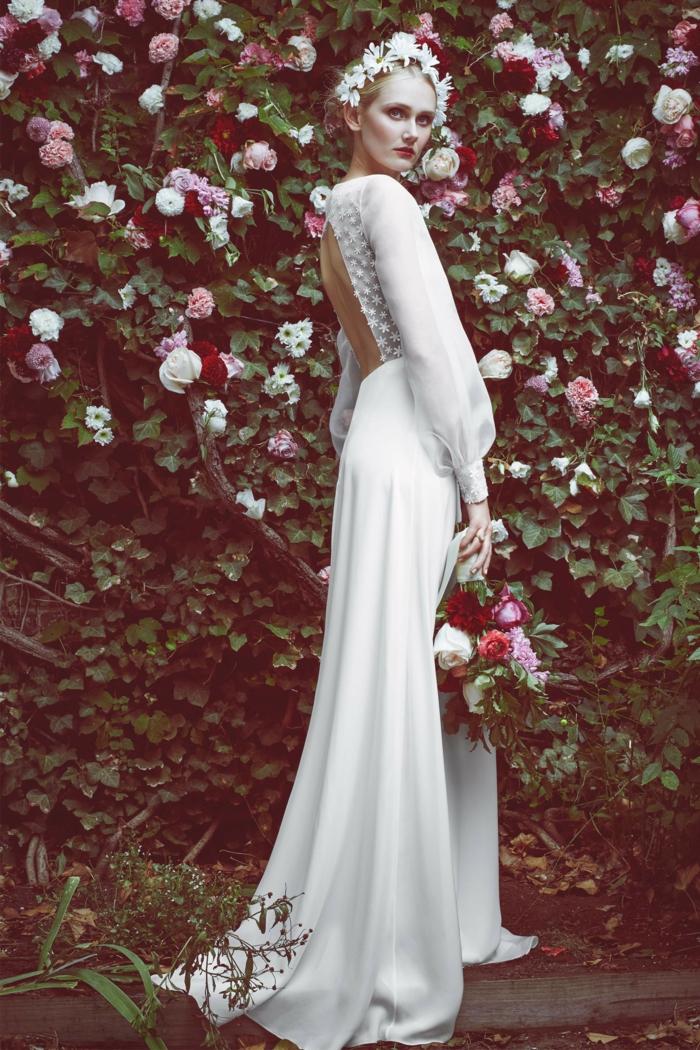 largo vestido en blanco con espalda descubierta, mangas transparentes de visillo, corona de flores blancas en el pelo