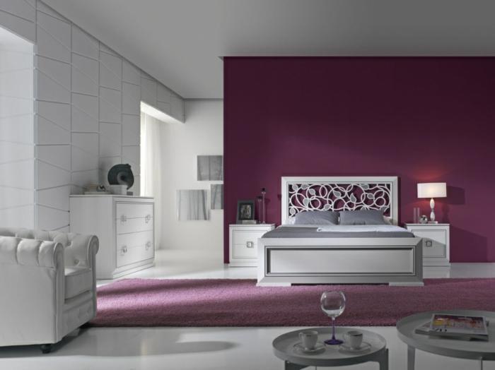 dormitorio matrimonial con paredes en morado y blanco con alfombra morada y cama blanca con decoracion floral