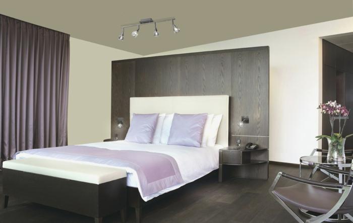 dormitorio matrimonial con cama con cabecera blanca y con paredes clara y techo más oscuro