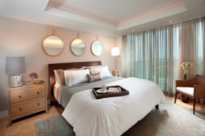 dormitorio para dos personas, con ventanas grandes con cortinas de color beige y espejos redondos