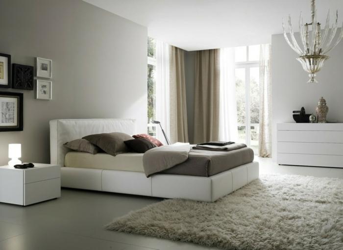 feng shui dormitorio con cama de cuero blanca con alfombra en color beige de pelos, araña de luces