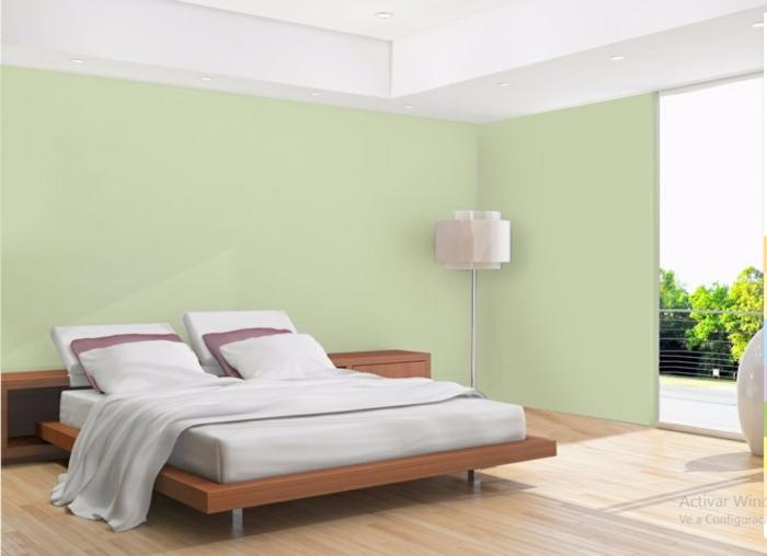 habitacion matrimonial con paredes en color verde claro, cama con sabanas blancas y cojínes en morado y blanco