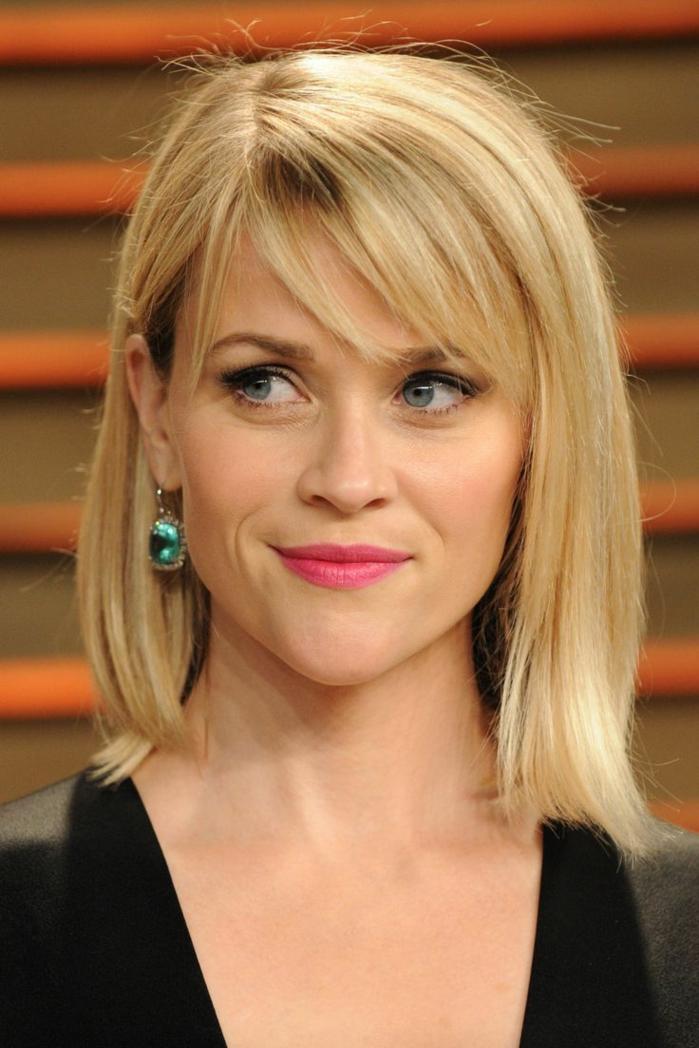 Reese Witherspoon, flequillo largo de lado, melena media rubia con pendientes con piedras verdes y vestido negro