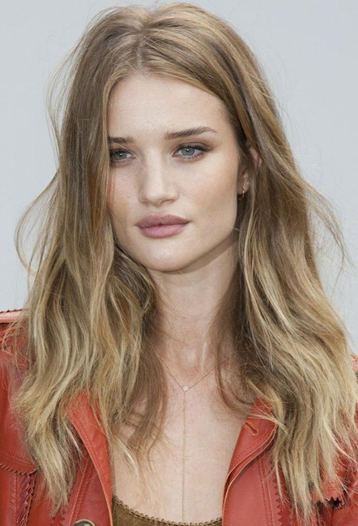 mechas californianas rubias, mujer de pelo largo con mechas rubias, de ojos azules con chaqueta de cuero