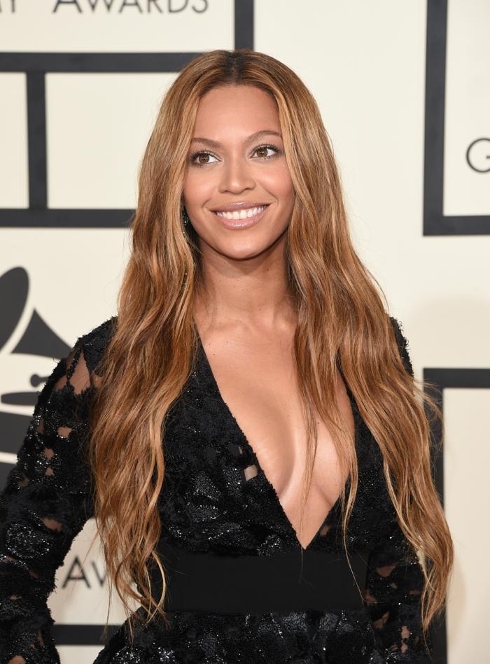 Beyonce con el pelo largo ondulado con mechas rubias doradas ideales para piel morena bronceada, mechas castañas