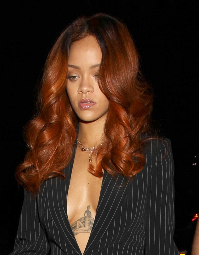 Rihanna con color de pelo cobrizo, largo y con ondulaciones, raíces oscuras, traje con negro, mechas castañas