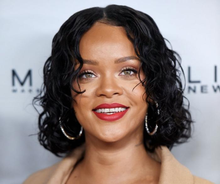 mechas color caramelo, Rihanna con corte de pelo bob chop rizado y negro con raya en el medio