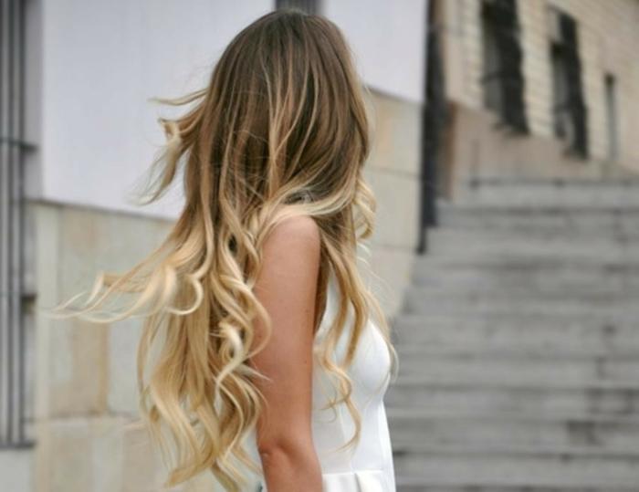 mechas o reflejos en pelo oscuro, modelo que se le ve solamente la parte de atrás, de pelo muy largo, rizado
