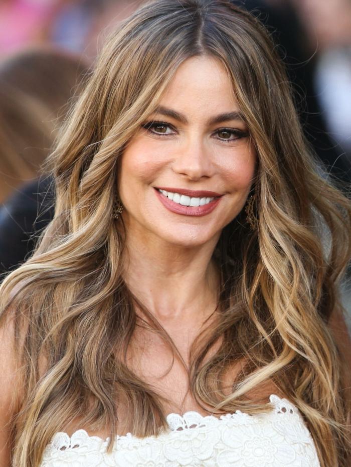 mechas o reflejos en pelo oscuro, modelo con pelo largo con mechas rubias, con la raya en el medio y labial rojo