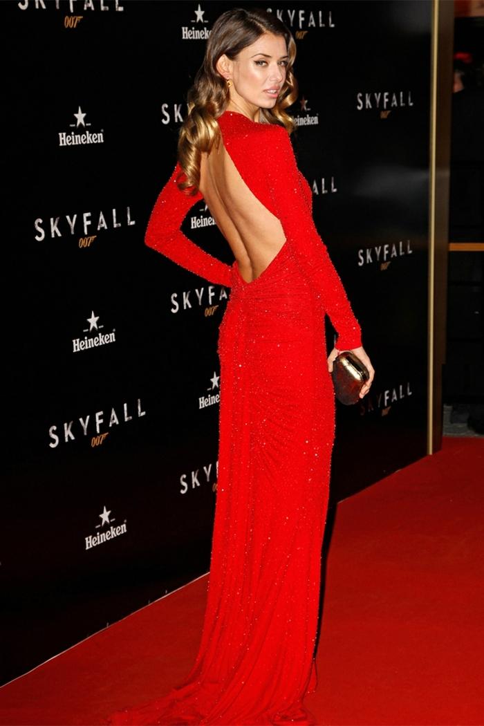 mechas o reflejos en pelo oscuro, modelo con vestido rojo largo con la espalda al descubierto y bolso dorado