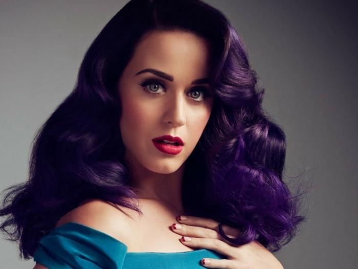 Katy Perry con color de pelo morado oscuro, vestida con vestido azul, mechas para pelo castaño