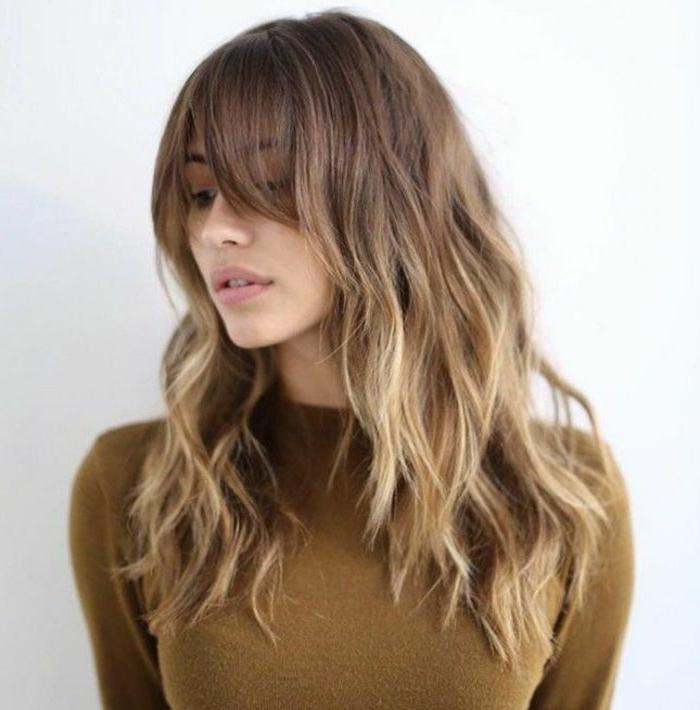 mechas rubias en pelo castaño, mujer con pelo ondulado castaño con mechas rubias californianas y flequillo