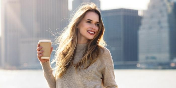 mechas rubias en pelo castaño, modelo con pelo largo con reflejos rubios y vaso de café de cartón en la mano
