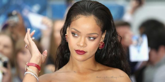 mechas rubias en pelo moreno Rihanna con color de pelo negro rizado, echado hacia atrás