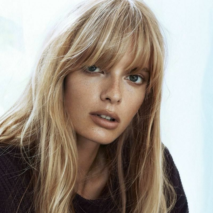 flequillo largo de lado, modelo con pelo rubio, melena larga con flequillo largo despeinado de ojos verdes