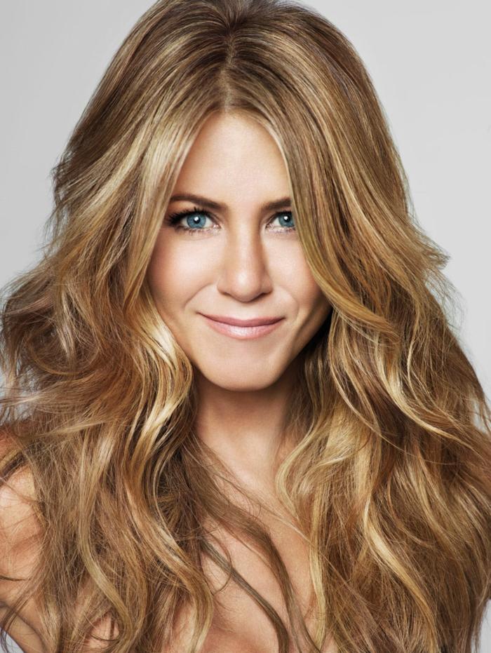 morenas con mechas Jennifer Aniston con el pelo largo ondulado con reflejos rubios y raya en el medio