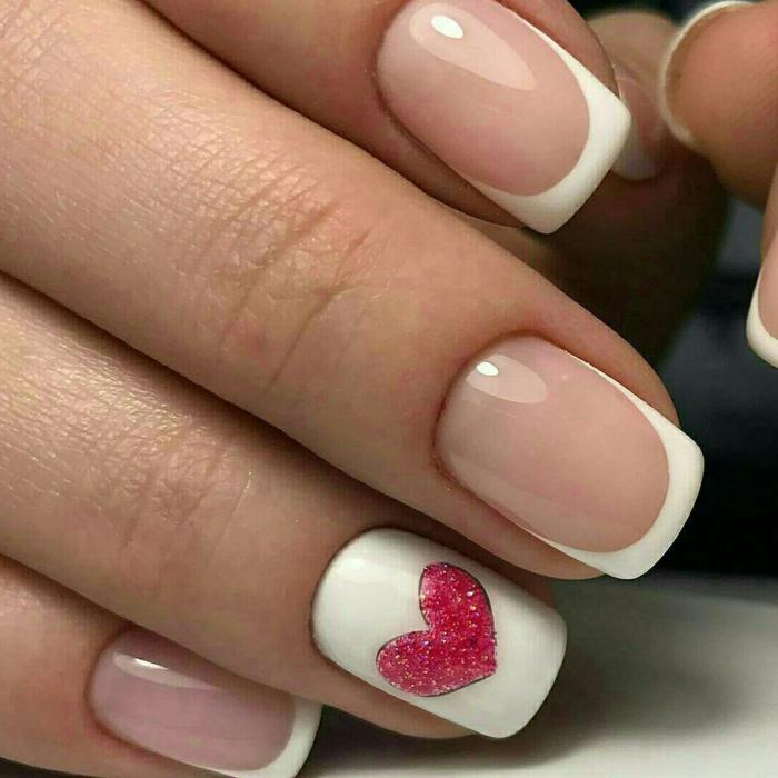 uñas manicura francesa clásica con pequeño detalle en el dedo anular, corazón en rojo purpurina