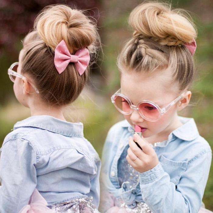 peinados faciles media melena, niña con moño alto con el pelo rubio y con cinta rosa en la cabeza