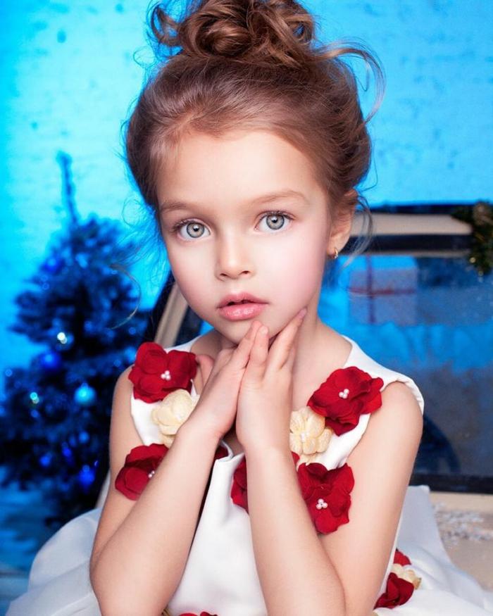 peinados fáciles y bonitos, niña con moño alto y pelo ondulado con ojos verdes y vestido blanco con flores rojas