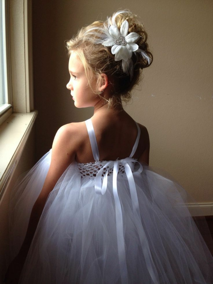 peinados faciles y rapidos, niña con el pelo en un moño alto decorado con una flor grande, vestido blanco