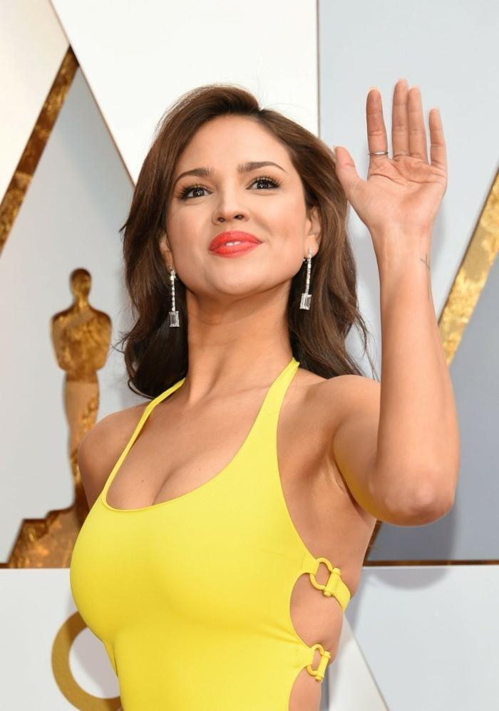 una morena clara con vestido amarillo en los Oscars, pendientes largos, pelo marron castaño mujer 2018
