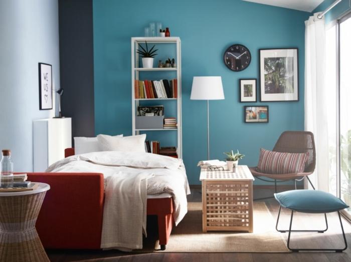 pintar habitacion juvenil con paredes en azul claro y azul oscuro con cama-sofá en rojo con sábanas blancas