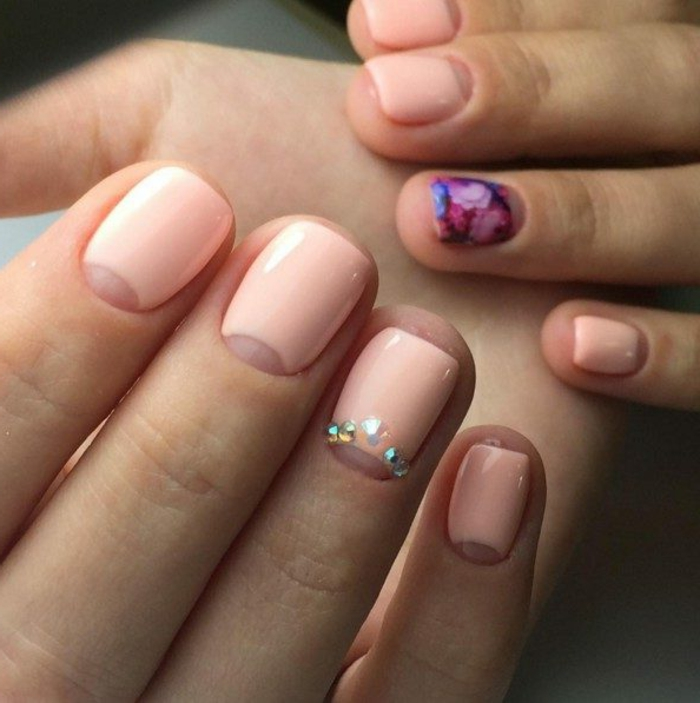 uñas cortas ovaladas pintadas en esmalte color rosado pastel, decoraciones en los dedos anulares