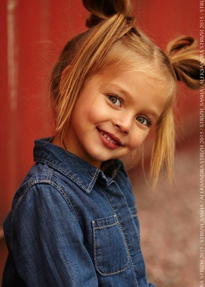 recogidos faciles niña con el pelo en moños altos de pelo rubio con la camisa de jeans con bolsillos