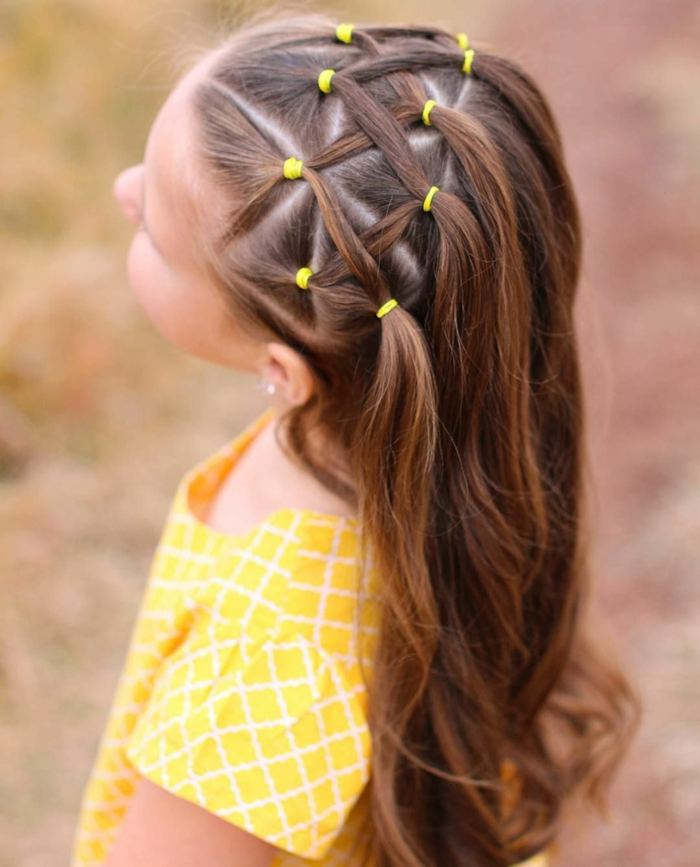 recogidos pelo largo, niña con gomas de pelo amarillas con el pelo con mechas entrelazadas formando figura