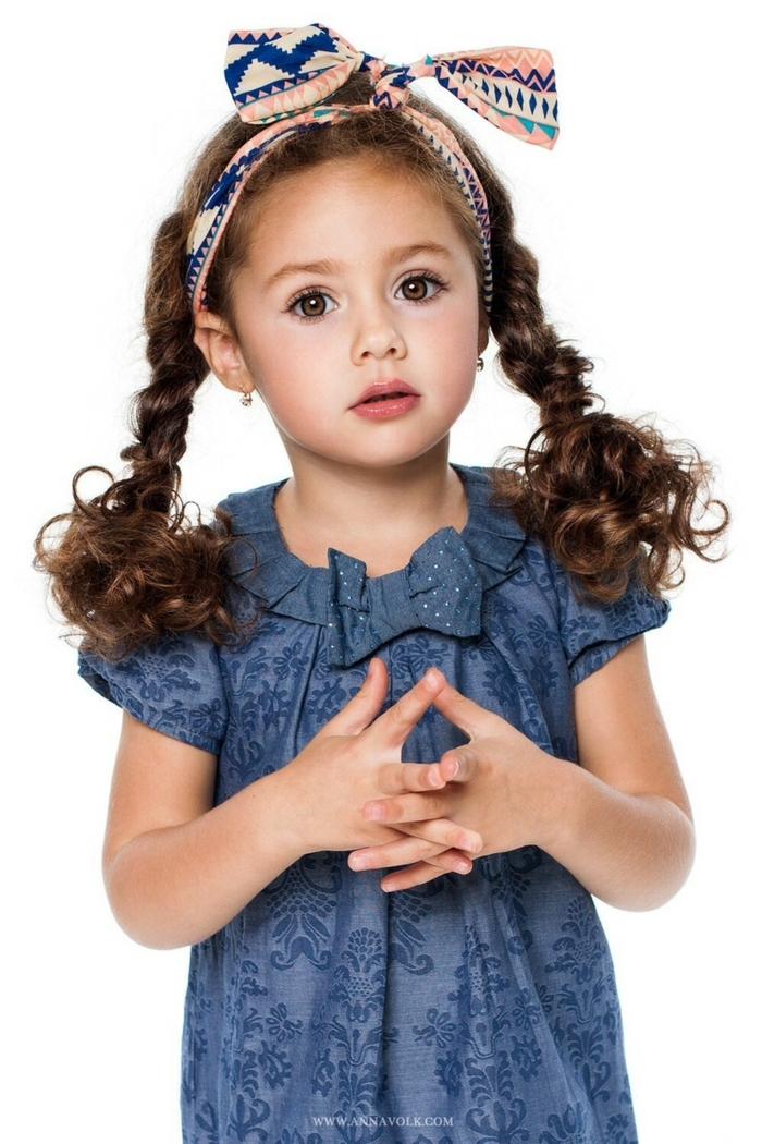 recogidos pelo largo, niña con diadema de tela de motivos etnicos con vestido azul con cinta, pelo rizado