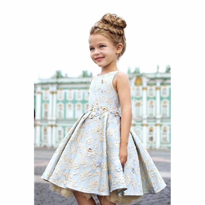 recogidos pelo largo niña con vestido elegante con moño alto con trenza gruesa delante sonriendo
