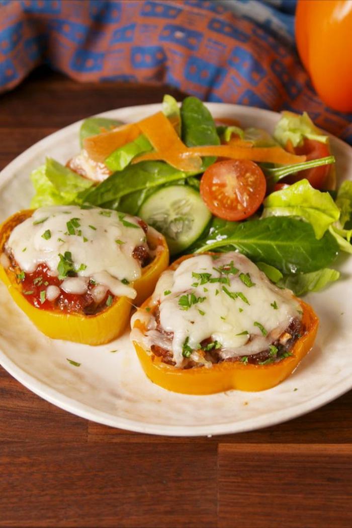 pimientos amarillos rellenos con carne molida, salsa de tomates y queso adornados de ensalada verde