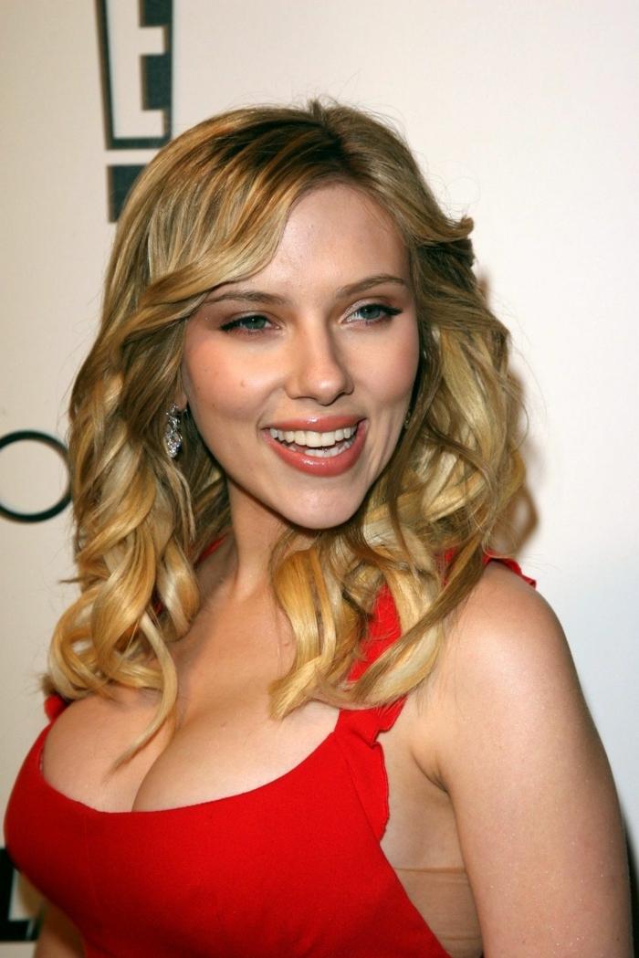 tintes rubios Scarlet Johansson con el vestido rojo de tirantes con volantes y escote grande, pelo rubio ondulado