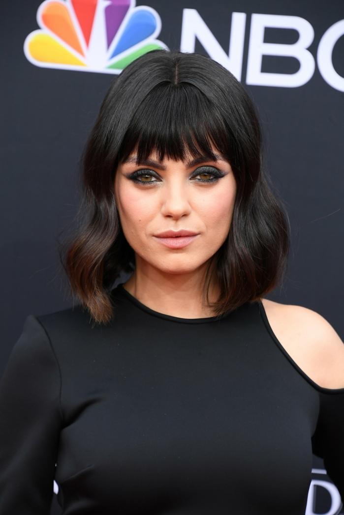 flequillo de lado, Mila Kunis con media melena con flequillo desafilado, pelo ondulado con rimel fuerte en negro