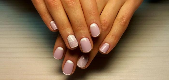 uñas cortas color pastel rosado con delgada línea blanca en las puntas y media luna, elementos decorativos