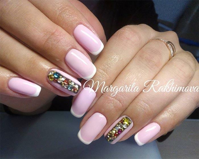 largas uñas en rosado pastel con línea blanca delgada y decoración de cristales coloridos en el dedo anular