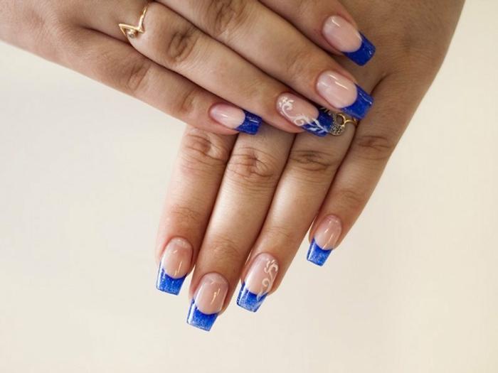 uñas largas francesas con puntas decoradas en azul oscuro, elementos florales en blanco