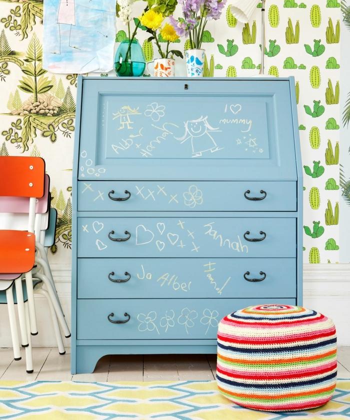 armario esquinero de color azul claro con otomana de colores y rayas con vinilo de cactus en la pared