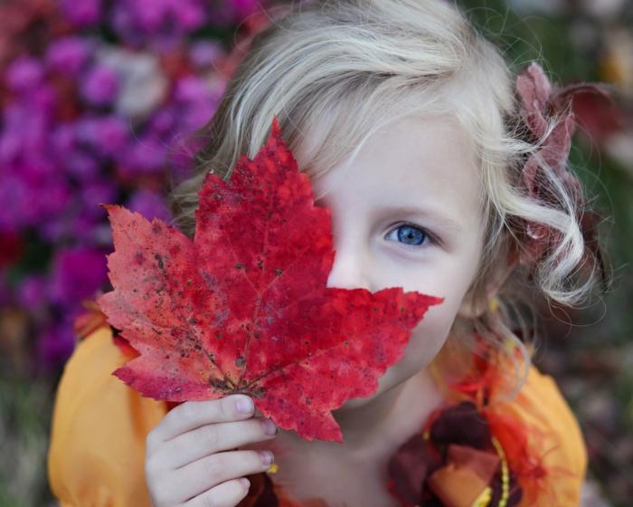 fotos de otoño gratis, niña rubia con pelo rizado con los ojos azules, hoja roja en la mano tapandose el ojo