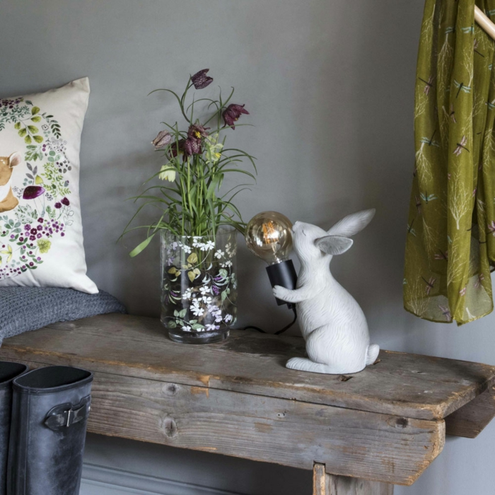 pisos modernos, lámpara de conejo blanco sujentando una bombilla, jarrón con flores