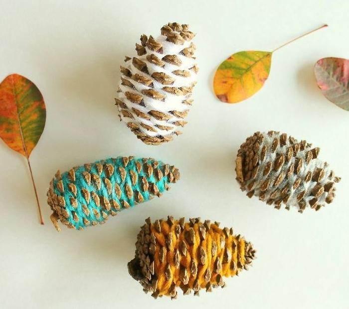 bonitas ideas de manualidades con piñas, piñas decoradas con hilo en diferentes colores