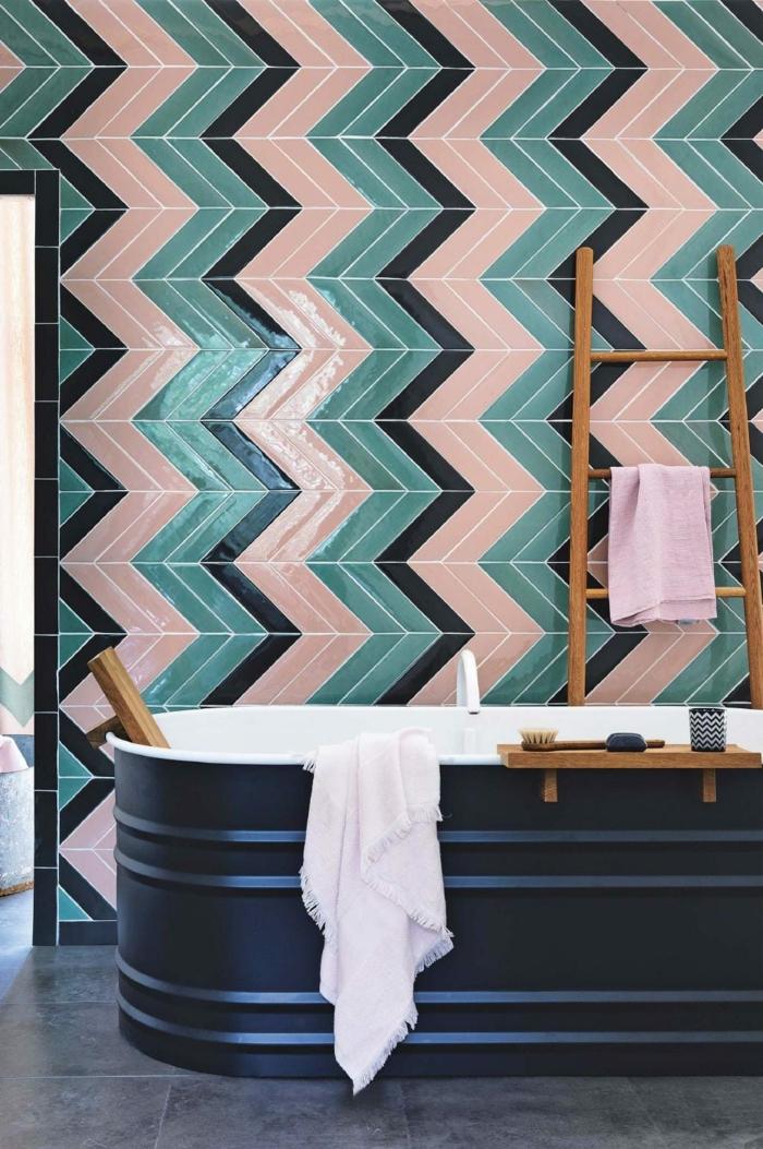 alicatar baño, bañera do color negro con toalla rosa dentro, escalera con toalla colgada, azulejos en forma de chevrón