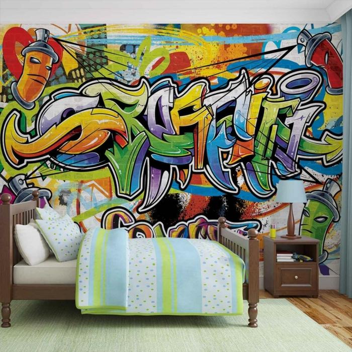 literas juveniles, cama de madera marrón con sabanas de colores azul, blanco y verde claro con pared de graffiti